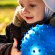 Portrait happy smiling child with blue ball in his hands — Stock Photo