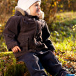 Cute child sitting on a stump — Stock Photo