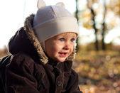 портрет милой радостное ребенка на фоне золотой характер — Стоковое фото