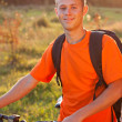 Happy man cyclist illuminated by sunlight — Stock Photo
