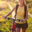 Happy woman cyclist illuminated by sunlight — Stock Photo