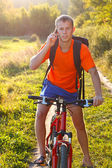 Man cyclist talking on call phone illuminated by sunlight — Photo