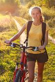 Glückliche frau radfahrer durch sonnenlicht beleuchtet — Stockfoto