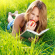 Happy Woman Reading Book with Apple in Hand — Stock Photo