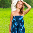 Beautiful young woman stand by leaned against a birch tree — Stock Photo