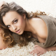 Sweet young girl laying on carpet she looks in to the lens — Stock Photo #10071945
