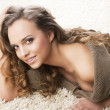 Sweet young girl laying on carpet she smiles — Stock Photo