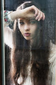 The thinking woman at window, she looks down at left — Stock Photo