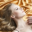Portrait of blond woman laying, she looks up at left - Stock Photo