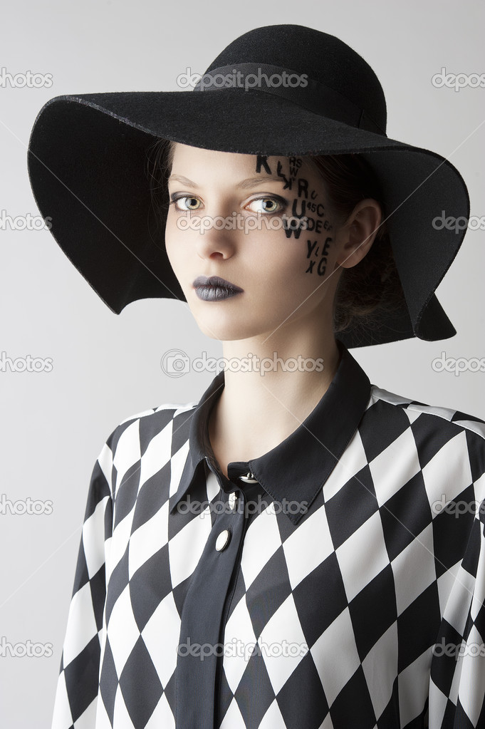 Pretty and beautiful young lady with a creative make up made with letter on face and black hat and unusual shirt, she is lightly turned of three quarters at right and looks in to the lens with serious expression — Stock Photo #10207008