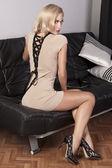 Sensual chica sentada en un sofá de cuero negro — Foto de Stock