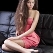 Brunette in pink on sofa, she has right hand on the right leg — Stock Photo