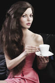 Sophisticated lady drinkig tea, she takes a cup of tea with both — Stock Photo