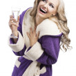 Blond haooy girl in bathrobe drinking champagne, she laughs and - Stockfoto
