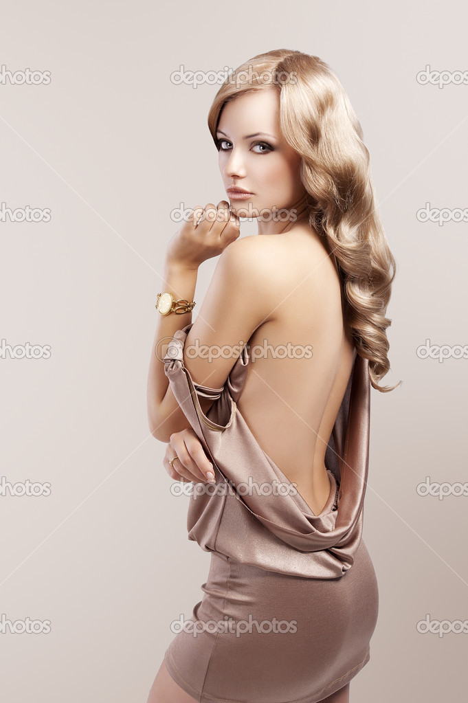 Very beautiful and attractive young blond woman in elegant silk dress and with old fashion hair style and golden clock on wrist — Stock Photo #8332638
