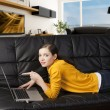 Girl on sofa with laptop, she indicates the display with one fin — Stock Photo