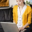 Girl on sofa with laptop, she 's on her knees on the sofa — Stock Photo #8546549