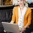 Stock Photo: Girl on sofa with laptop, she smiles and looks in to the lens