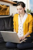 Girl on sofa with laptop, she 's on her knees on the sofa — Stock Photo