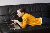 Ragazza sul divano con il portatile, lei guarda il display — Foto Stock