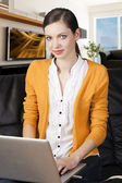 Girl on sofa with laptop, she's smile and look in to the lens — Stock Photo