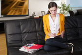 The girl reading a book, she 's on her knees on the sofa — Stock Photo