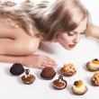 Blond sexy girl eating pastry, she looks pastries — Stock Photo