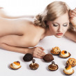 Blond sexy girl eating pastry, she has right hand near her head - Stock Photo