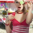 Fashion summer girl drinking, she covers her left eye with lolli — Stock Photo #8901148