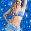 Swimsuit and balloons in blue, her left arm is on the head — Stock Photo #9177561