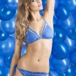 Swimsuit and balloons in blue, her left arm is on the head — Stock Photo #9177578
