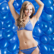 Swimsuit and balloons in blue, both her arms are raised — Stock Photo #9177594