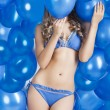 Swimsuit and balloons in blue, her face is behind one balloon - Foto Stock
