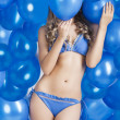 Swimsuit and balloons in blue, her face is behind one balloon - Stock Photo