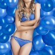 Swimsuit and balloons in blue, she looks up at left — Stock Photo #9177636