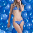 Swimsuit and balloons in blue, she has left hand on the face — Stock Photo #9177640