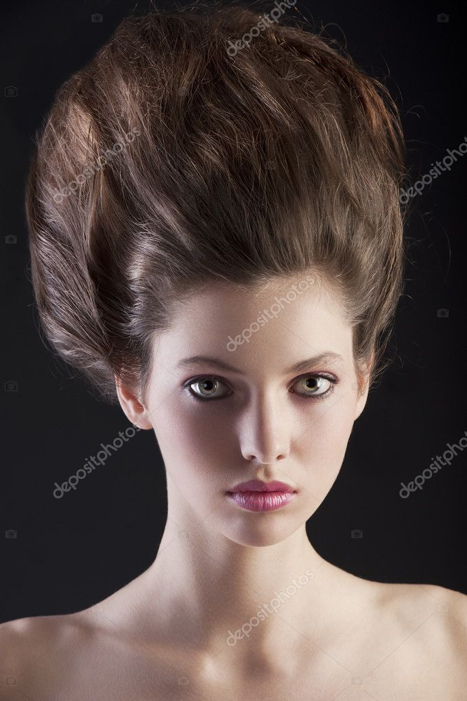 Close up portrait of young beautiful woman with dark hair and creative hairstyle posing an black background — Stock Photo #9338792