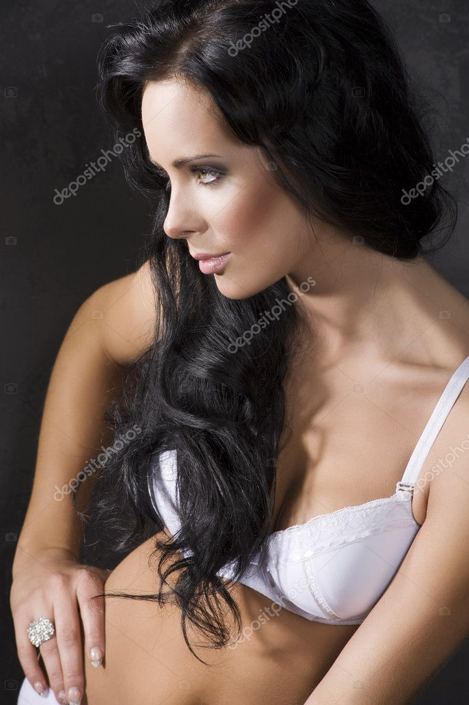 Portrait of young pretty brunette with white bra against a dark background  Stock Photo #9570778