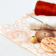 Stock Photo: Beige spool of thread and buttons on a floral fabric