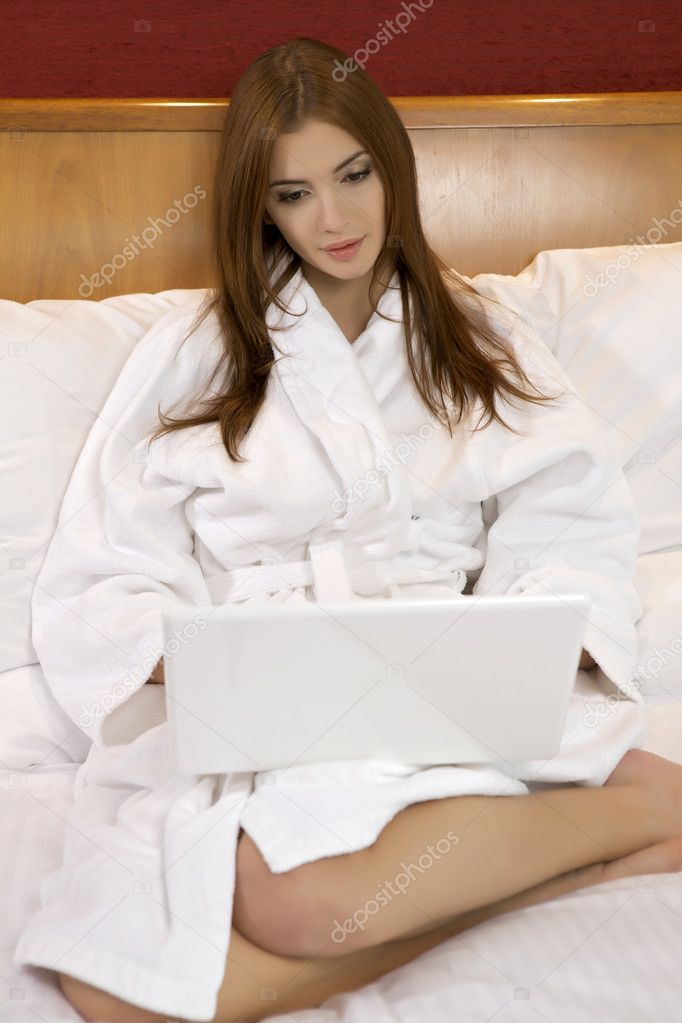 Portrait of beautiful brunette woman with laptop on bed at bedroom — Stock Photo #10140546
