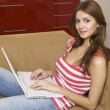 Young woman lying on a white sofa with a laptop. - Stok fotoğraf