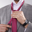 Portrait of businessman tying tie - Photo