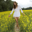 Brunette woman in a yellow flowers field - Photo