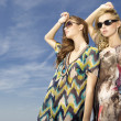 Two beautiful girl in sunglasses on background blue sky — Stock Photo #10612098