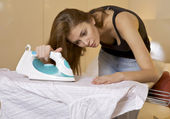 Young woman ironing on ironing board — Stock Photo