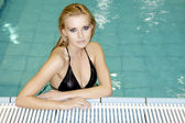 Beautiful young woman standing in a swimming pool — Stock Photo