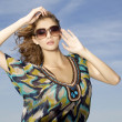 Beautiful girl in sunglasses on background blue sky — Stock Photo #8529149