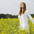 Brunette woman in a yellow flowers field - Stockfoto