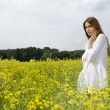 Brunette woman in a yellow flowers field - Foto Stock
