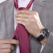Portrait of businessman tying tie - Stock Photo